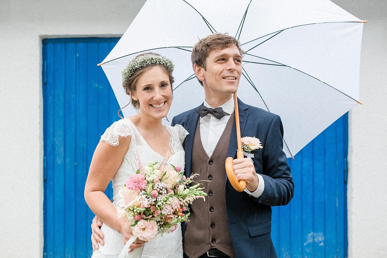 Hochzeit bei Regen Brautpaar mit Regenschirm