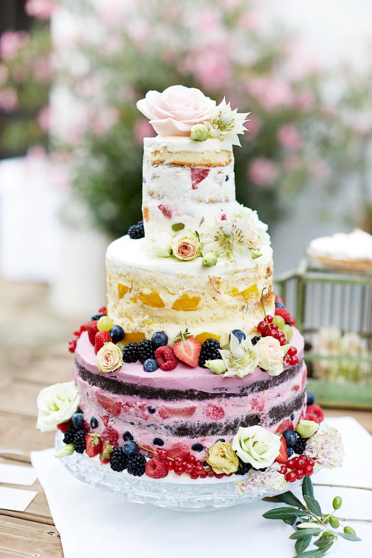 Hochzeitstorte bunt sommerlich, dreistöckiger Semi Naked Cake in bunten Farben mit Beeren